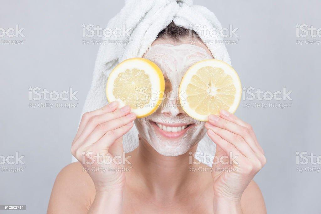 Lächelnde Brünette Frau mit zwei Zitronenscheibe vor ihr Gesicht. Frau mit feuchtigkeitsspendenden Gesichtsmaske. Schönheit und Hautpflege Pflegekonzept. – Foto