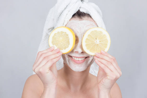Smiling brunette woman holding two slice of lemon in front of her face. woman with moisturizing facial mask. Beauty and skin care concept. - foto stock