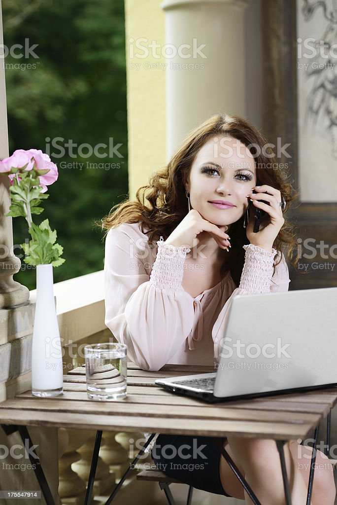 \'Smiling brunette Woman with Notebook and Handy at Table,...