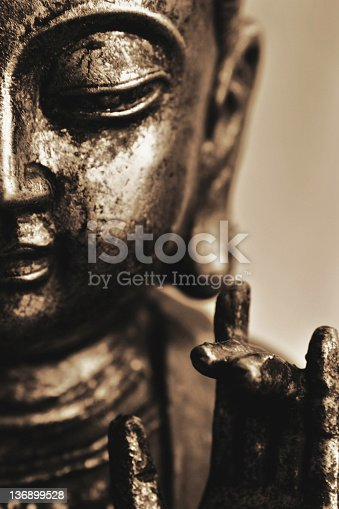 smiling buddha in close-up with karana hand gesture, vertical frame