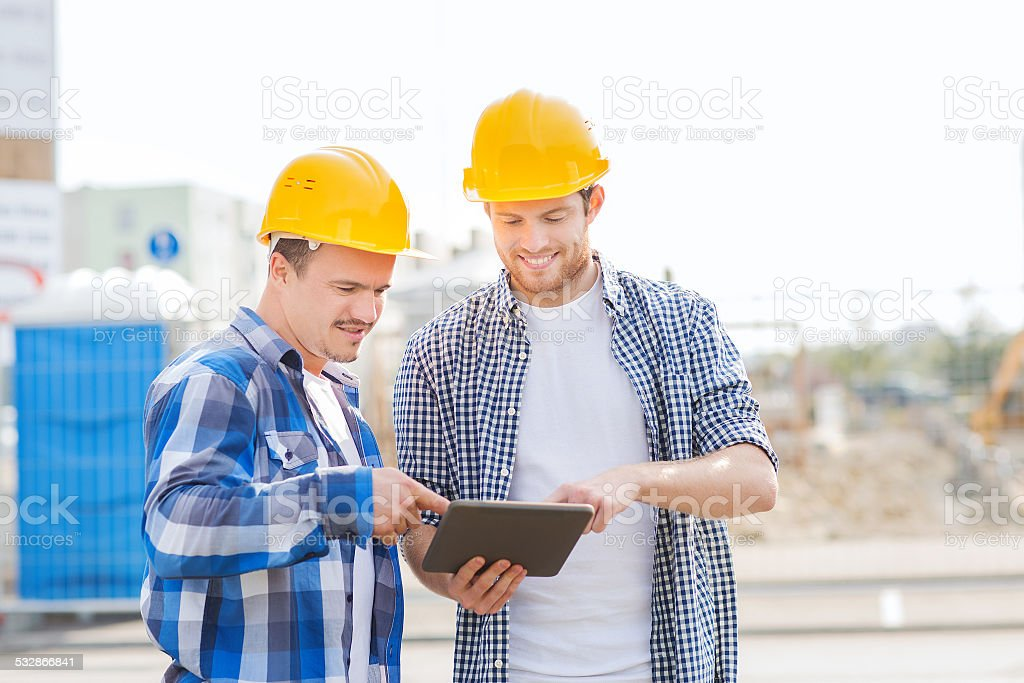 smiling builders in hardhats with tablet pc stock photo