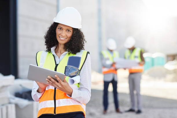 Smiling building engineer using a tablet on her construction site stock photo