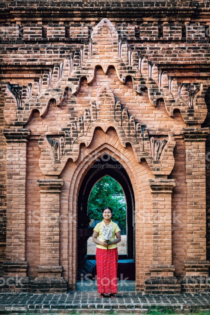 Smiling Burmese Woman with Flower Bouquest Temple Entrance Bagan Myanmar stock photo