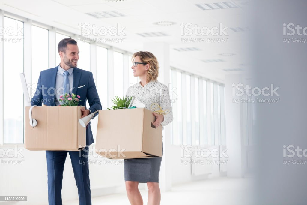 Smiling business colleagues carrying cardboard boxes at new office