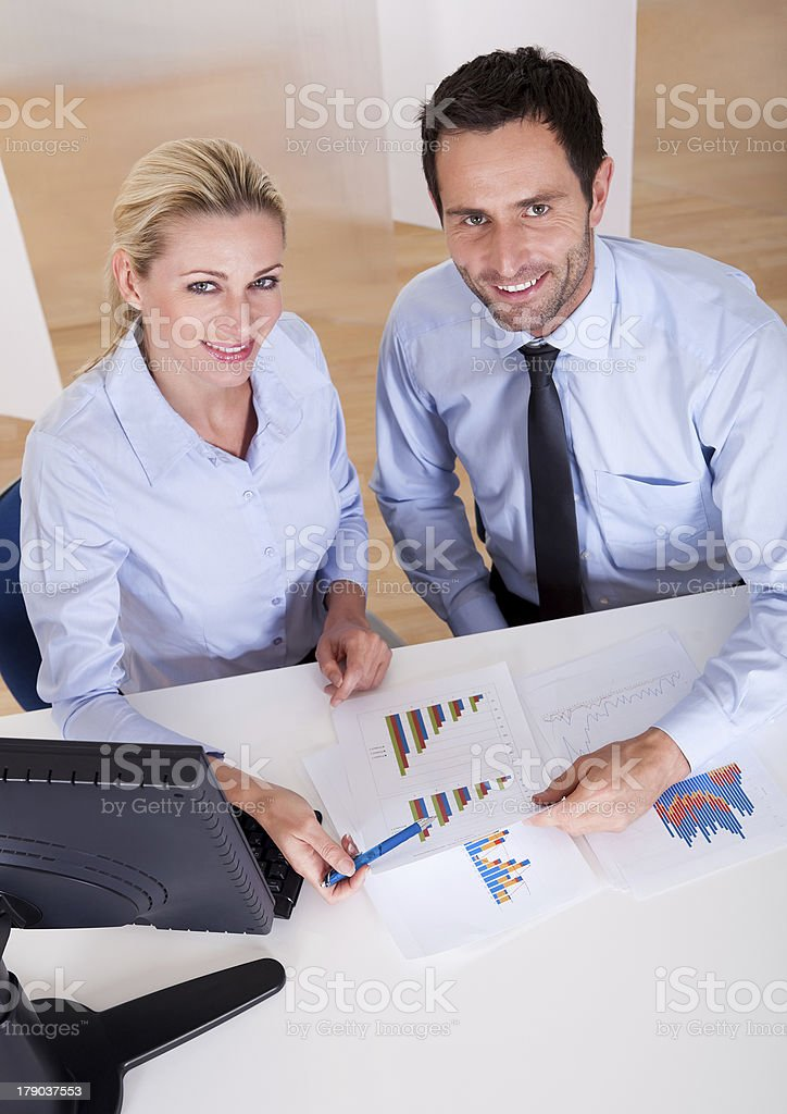 Smiling business colleagues discussing statistics royalty-free stock photo