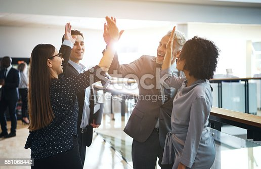 istock Smiling business colleagues high fiving each other in an office 881068442