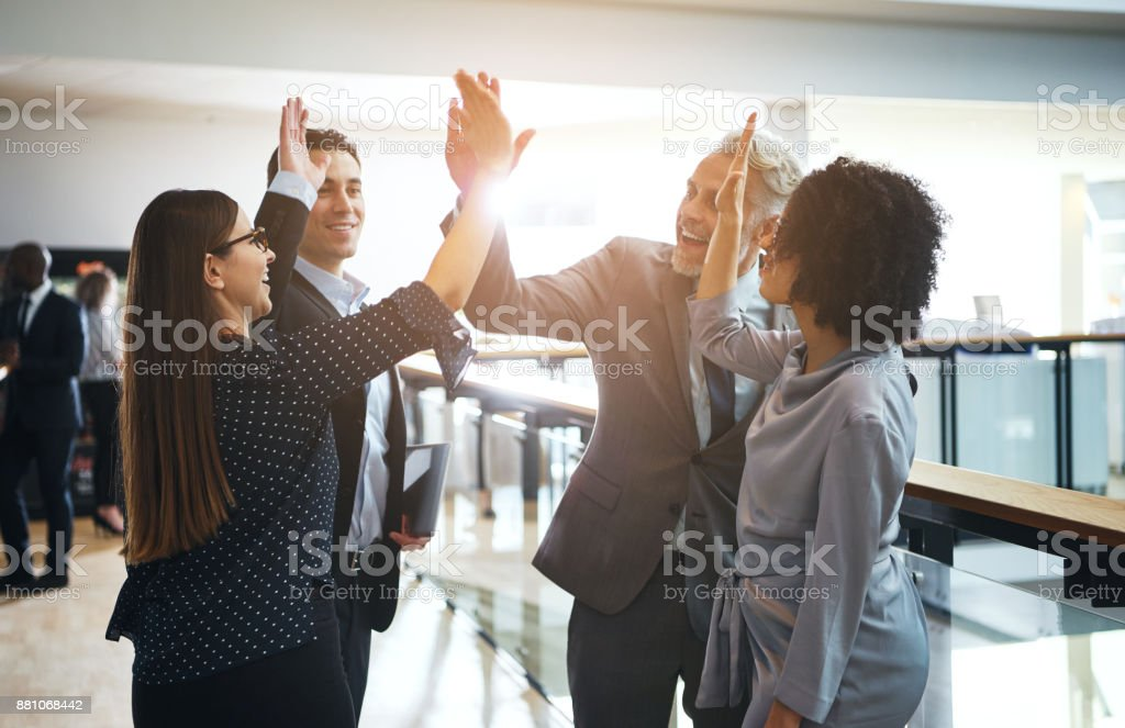 Smiling business colleagues high fiving each other in an office - foto stock