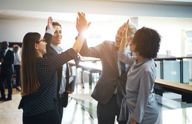 smiling business colleagues high fiving each other in an office - teamwork stock photos and pictures