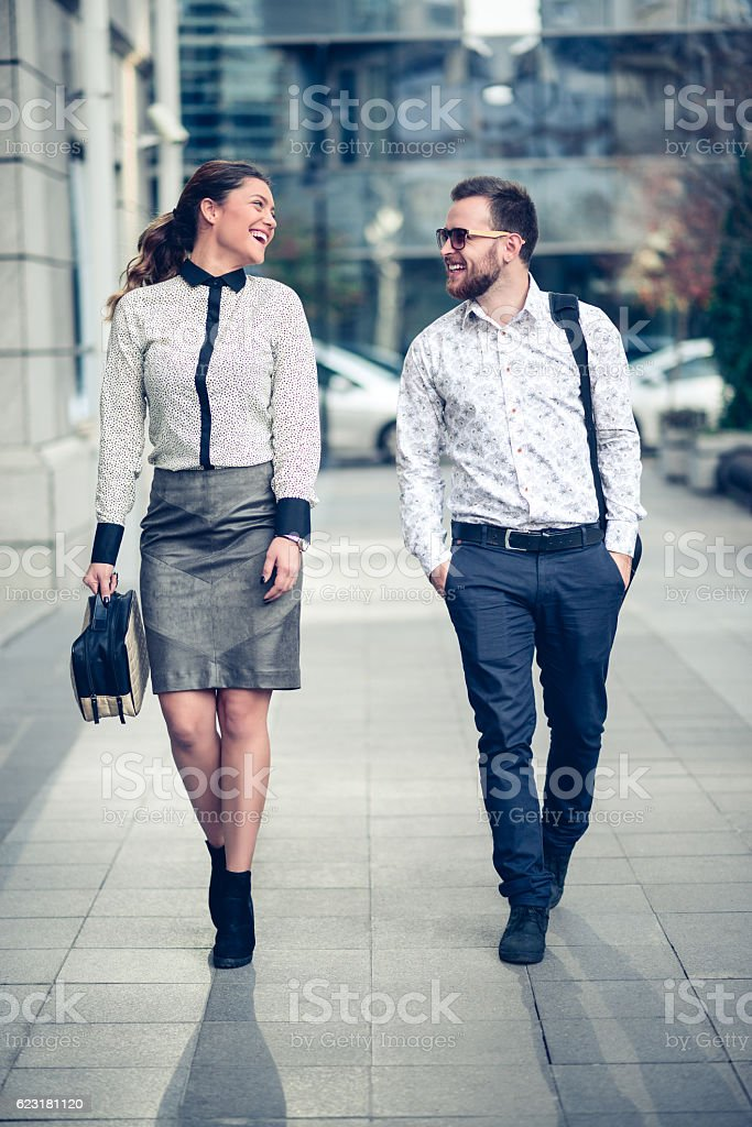Smiling Business Colleagues Walking on the Street and Talking stock photo