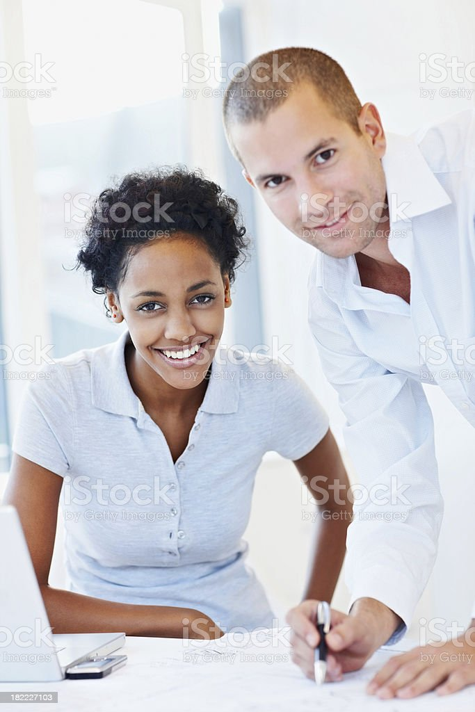 Smiling business colleagues working on a project royalty-free stock photo