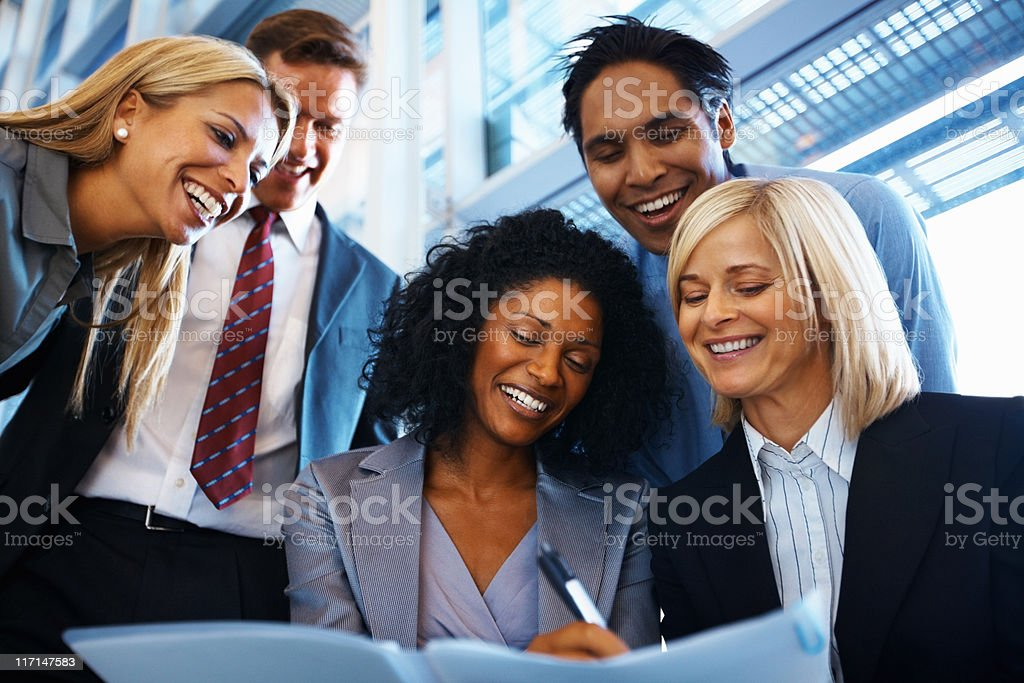 Smiling business colleagues working together on a project royalty-free stock photo