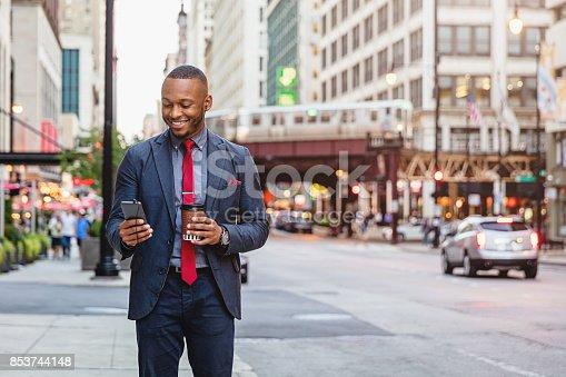 African american businessman using an App on his smart phone - reading new messages with a bright happy smile while walking in the streets of downtown Chicago. Downtown Chicago, Illinois, USA