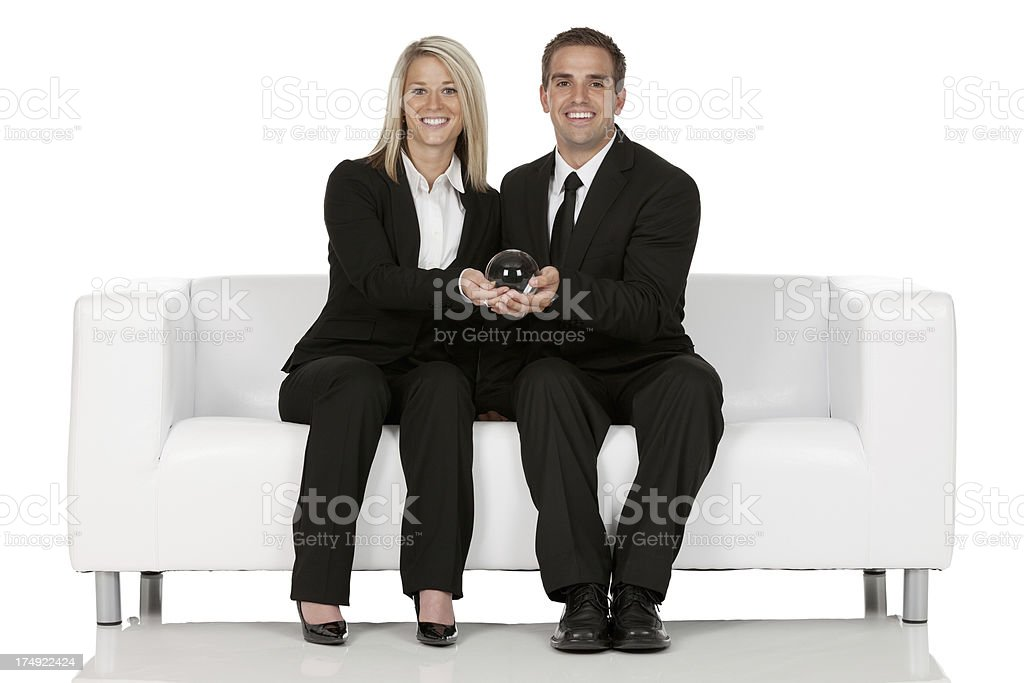 Smiling business couple holding a crystal ball royalty-free stock photo