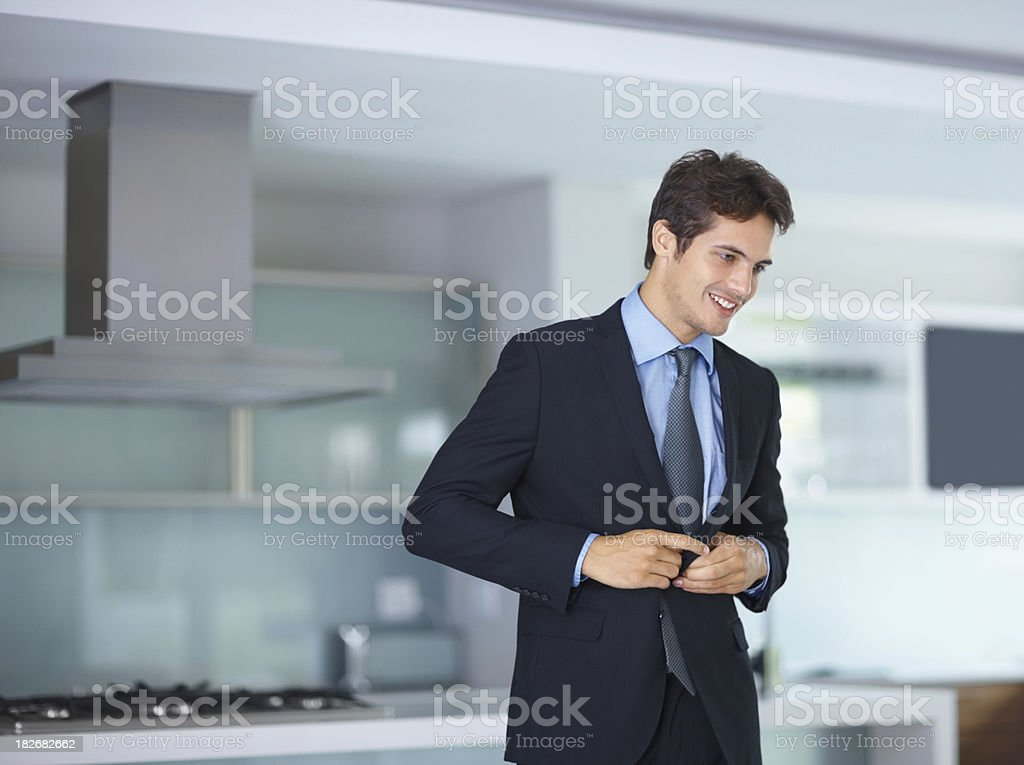 Smiling business executive buttoning his suit stock photo