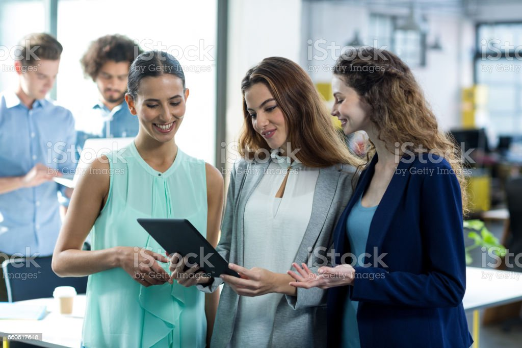 Smiling business executives using digital tablet at meeting royalty-free stock photo