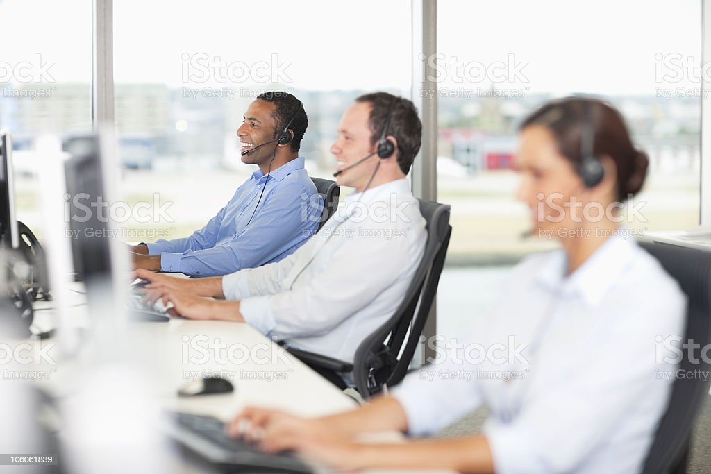 Smiling business executives wearing headset while sitting in office royalty-free stock photo