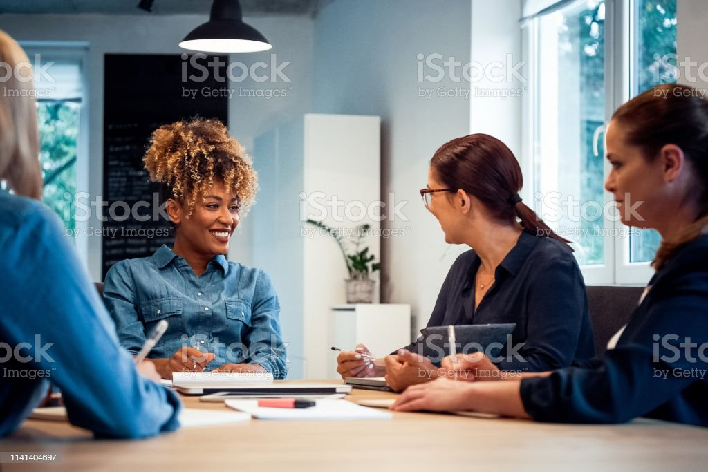 Smiling business expertise working together Smiling business expertise working together at desk. Confident businesswomen are planning new strategies. They are sitting in office. 35-39 Years Stock Photo