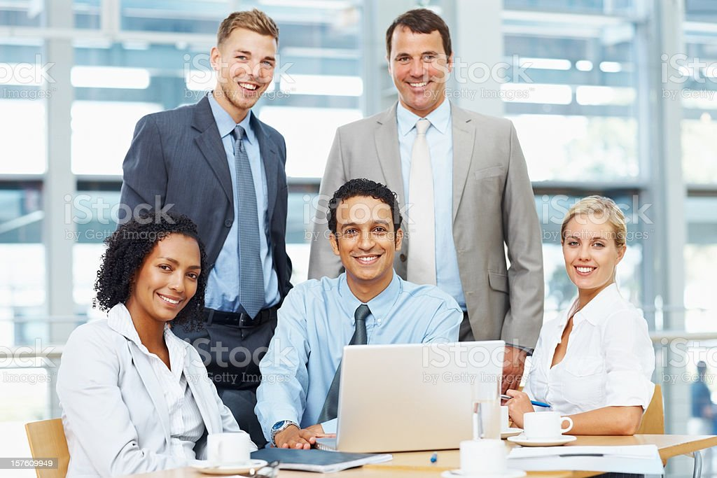 Smiling business group using a laptop at work royalty-free stock photo
