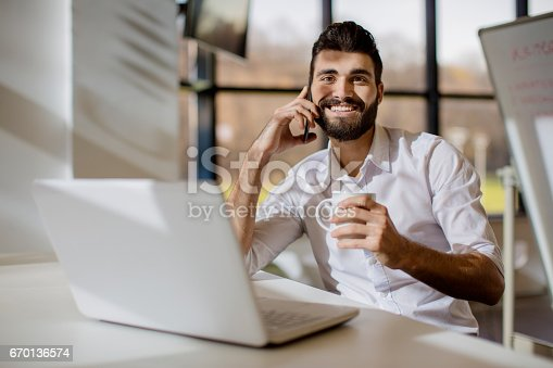 istock Smiling business man drinking coffee and using smartphone 670136574