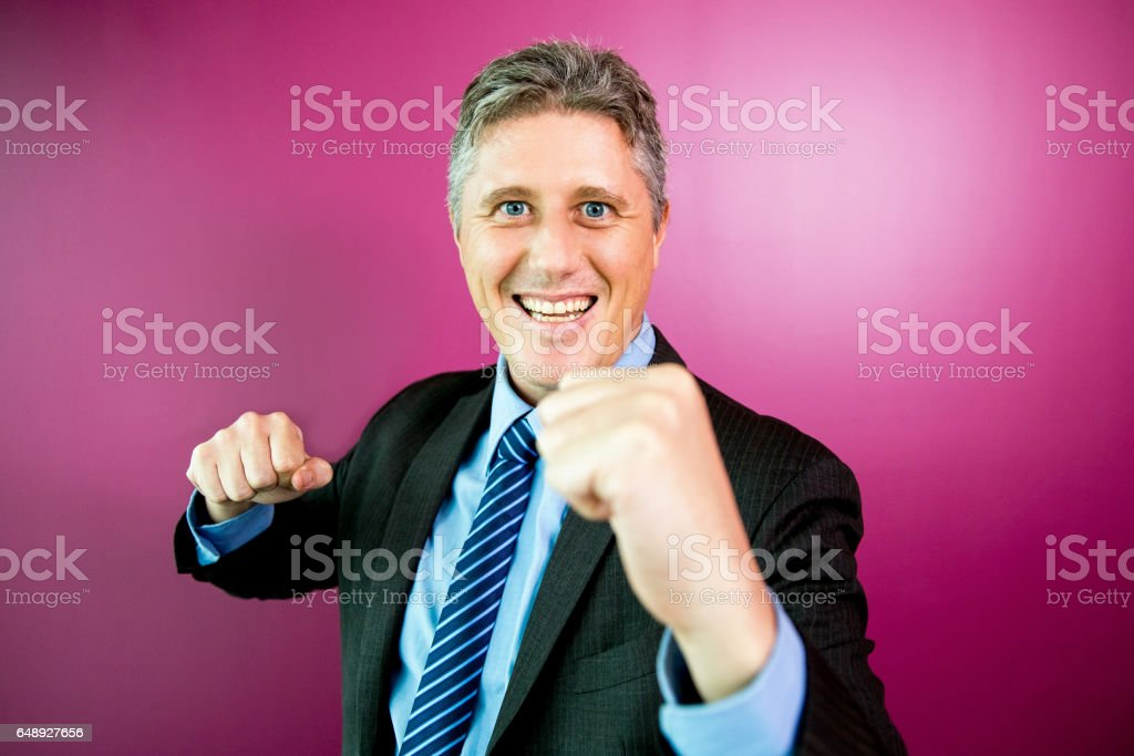 Smiling Business Man Fighting Against Viewer stock photo