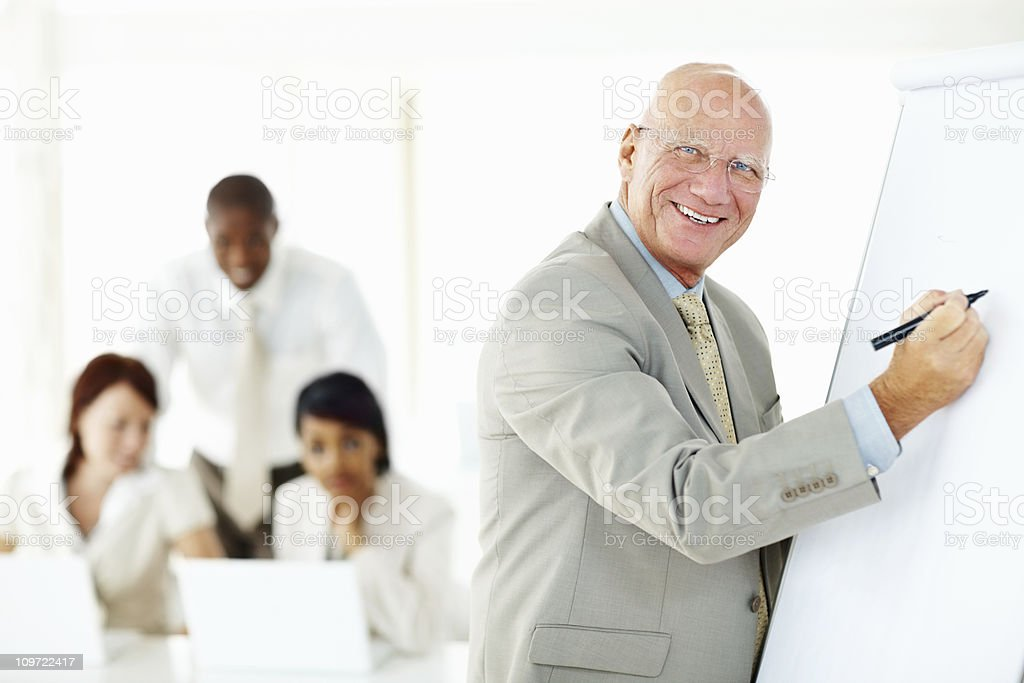 Smiling business man giving a presentation in board room royalty-free stock photo