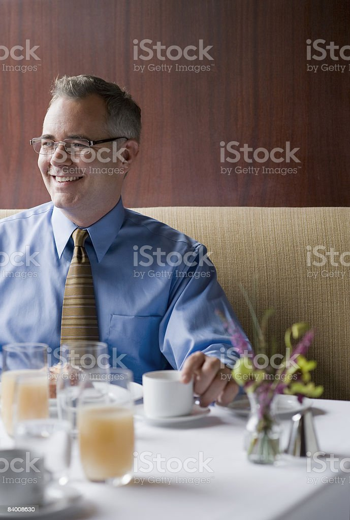 Smiling business man in a booth in a restaurant. royalty-free stock photo