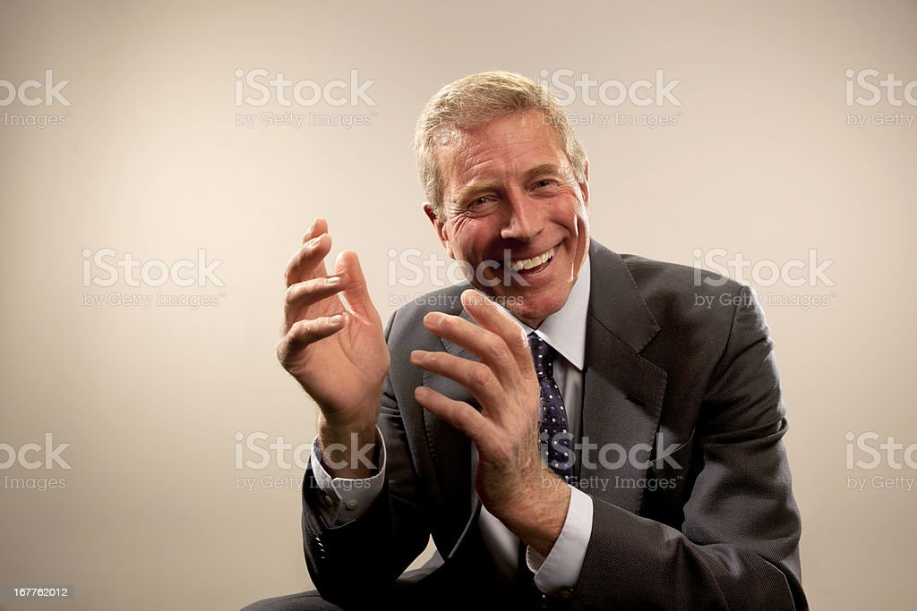 Smiling business man makes hand gestures royalty-free stock photo