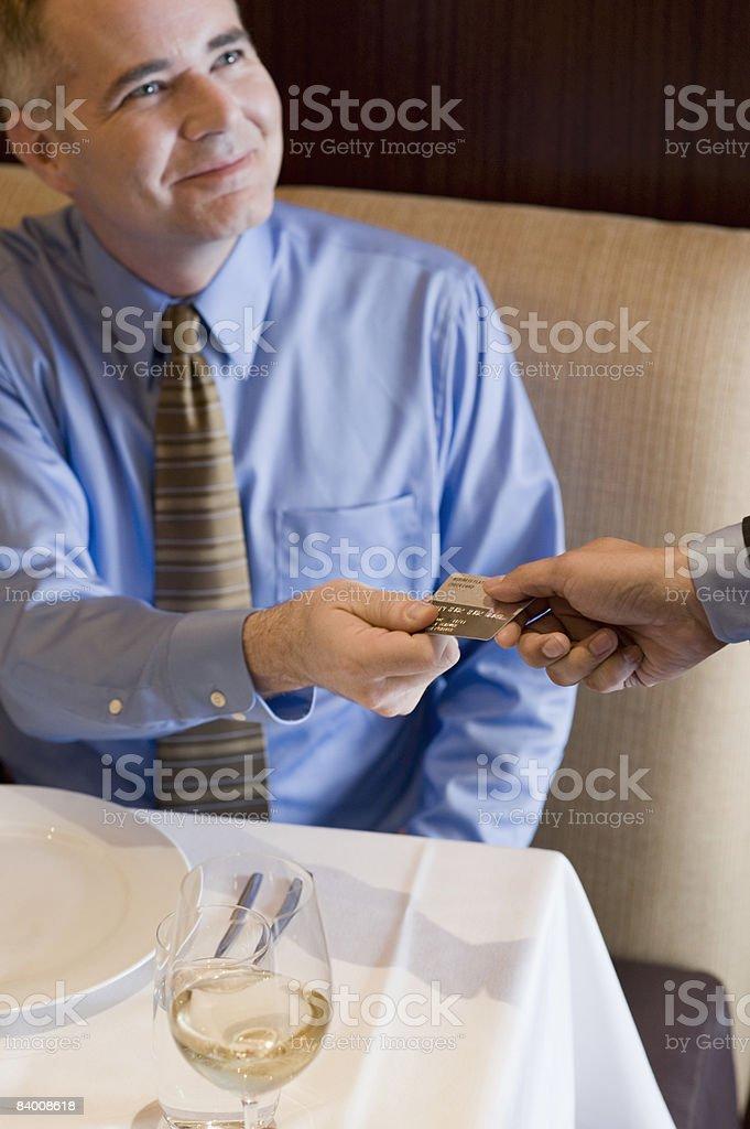 Smiling business man pays with credit card. royaltyfri bildbanksbilder