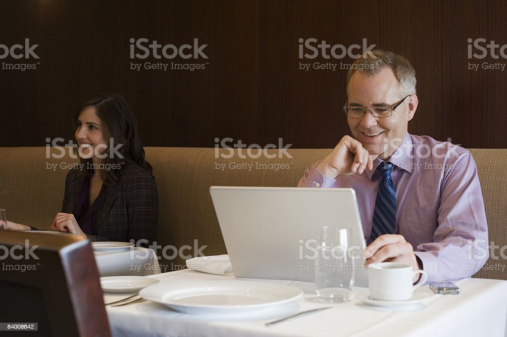 Smiling business man reads computer in restaurant  royalty-free stock photo