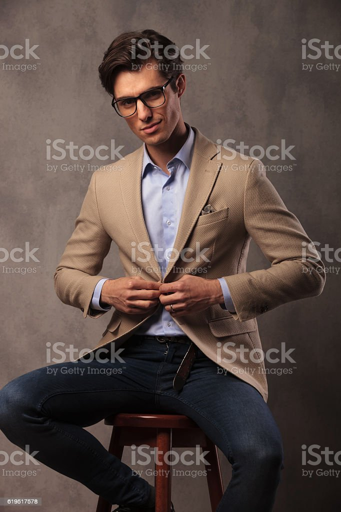 smiling business man sitting and unbuttoning his coat stock photo