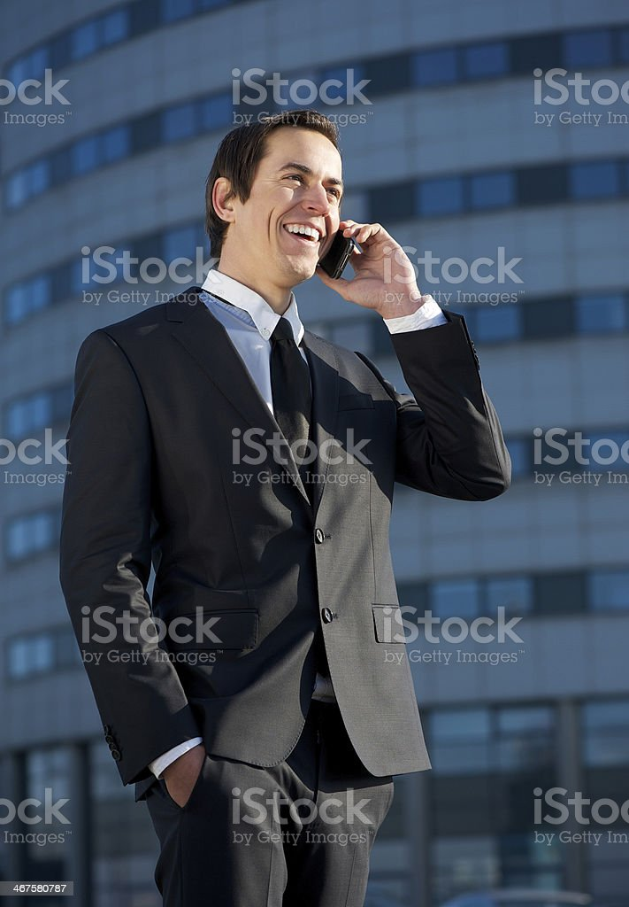 Smiling business man talking on mobile phone outdoors royalty-free stock photo