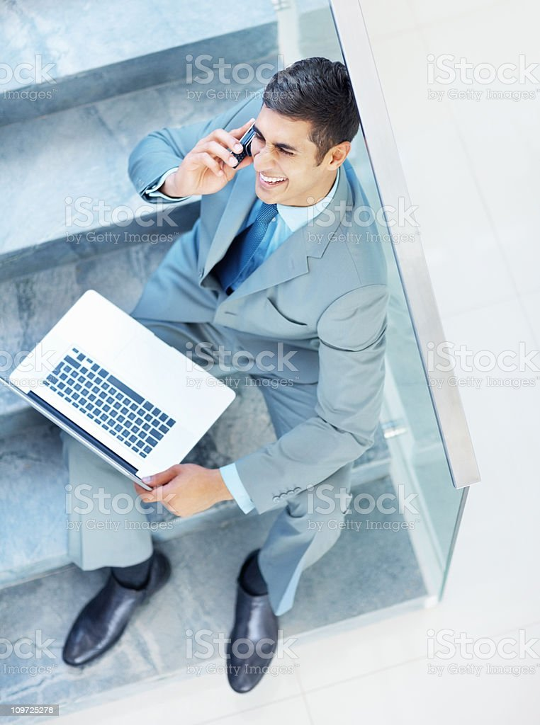 Smiling business man using a cellphone at the stairs royalty-free stock photo