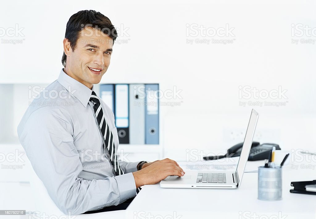 Smiling business man using a laptop at work royalty-free stock photo