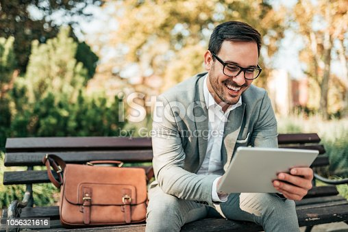 Smiling business man using tablet while sitting on the bench.