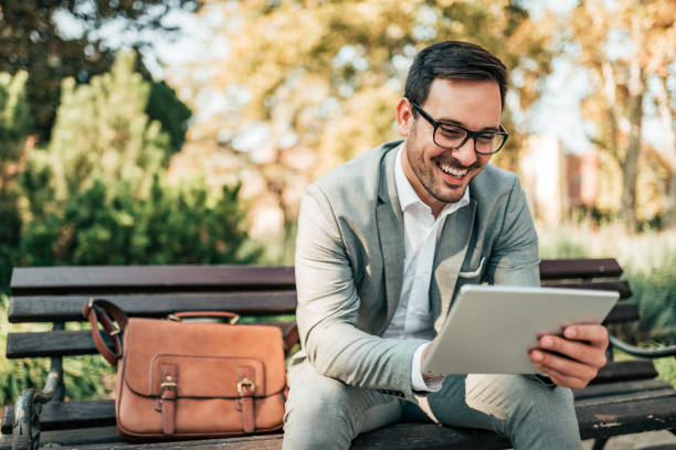 Smiling business man using tablet while sitting on the bench. stock photo
