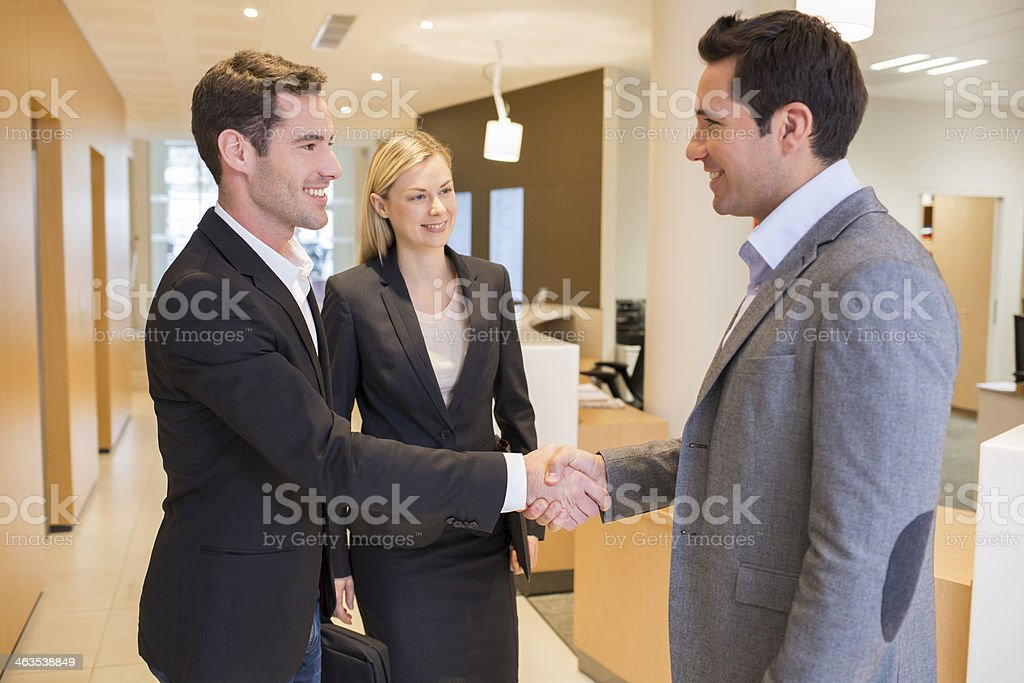 Smiling Business partners shaking hands in hall, lobby stock photo