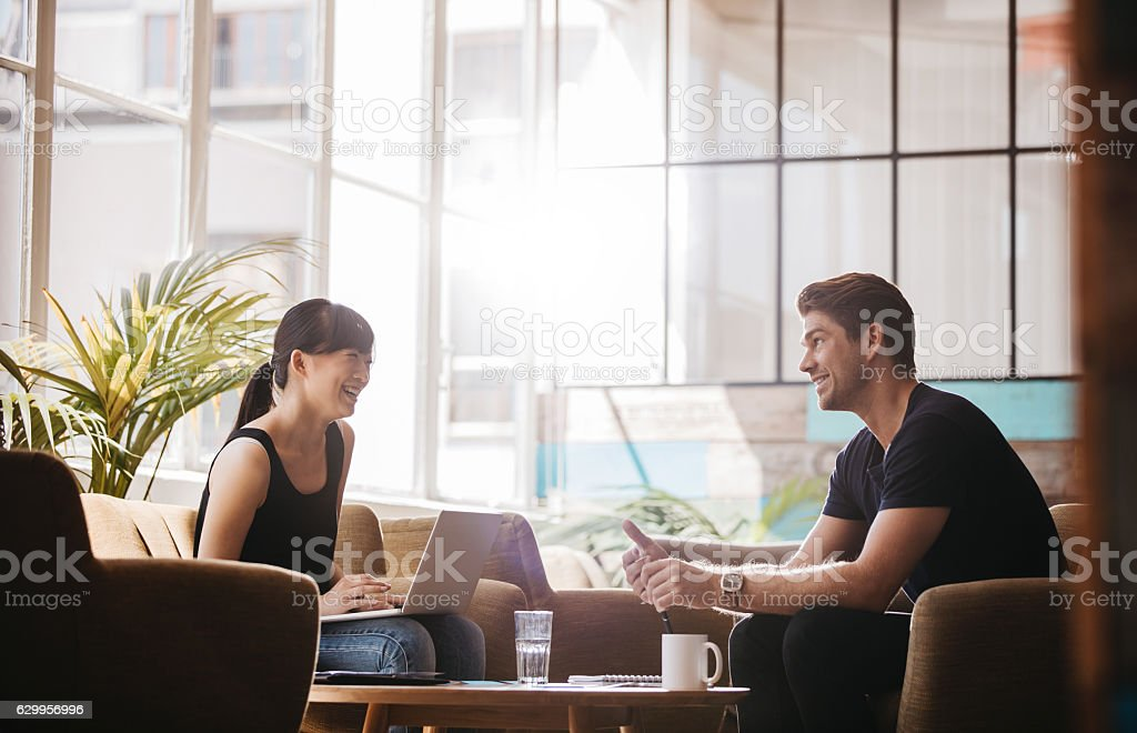 Smiling business partners working together in modern office stock photo
