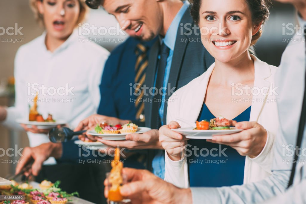 Smiling Business People and Snacks at Buffet Table stock photo