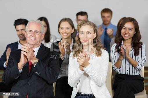 862718922 istock photo Smiling business people applauding to speaker after presentation 598098224