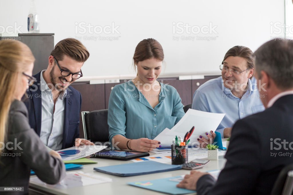 Smiling business people at meeting table stock photo