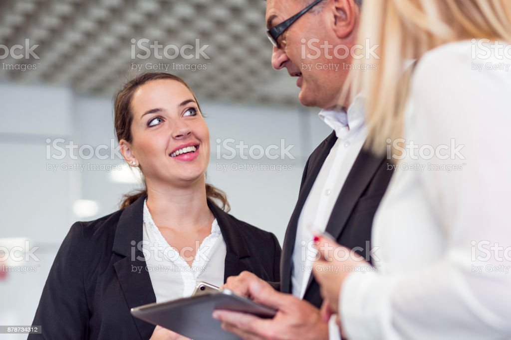 Smiling business people chatting in the lobby stock photo