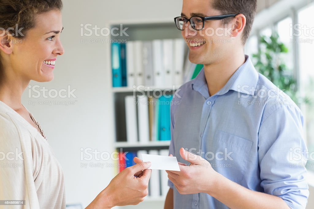 Smiling business people exchanging visiting card stock photo