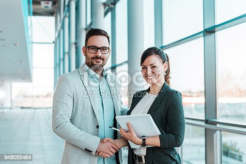 istock Smiling business people handshake after successful negotiation. Looking at camera. 948055464