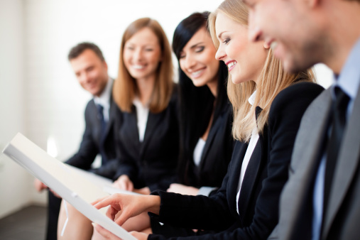 istock Smiling business people looking at same document 156606281