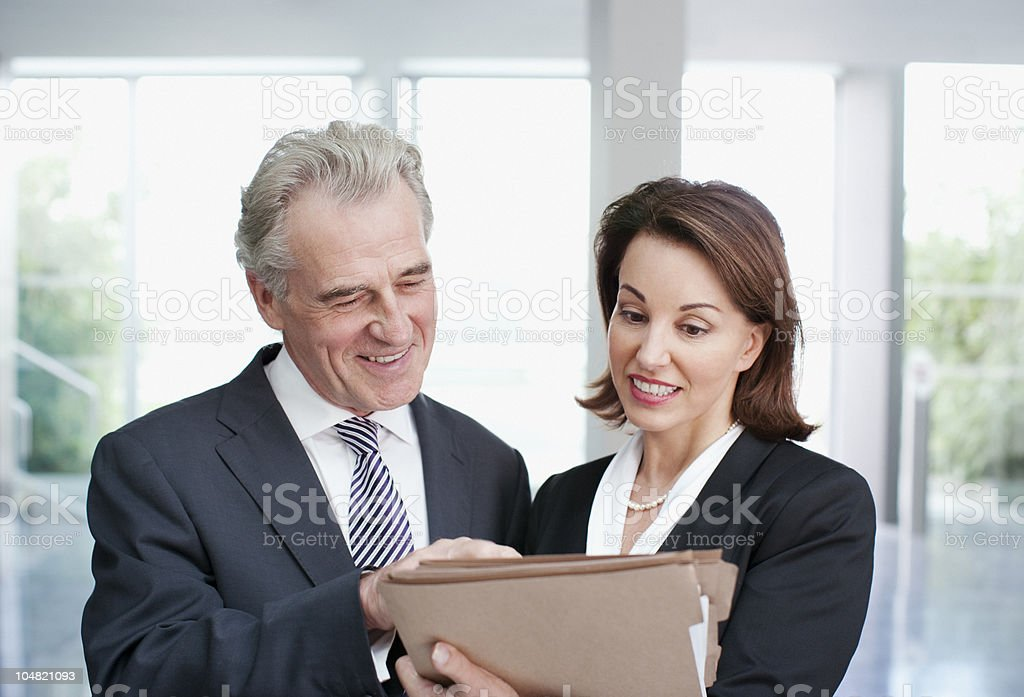 Smiling business people reviewing file in office royalty-free stock photo