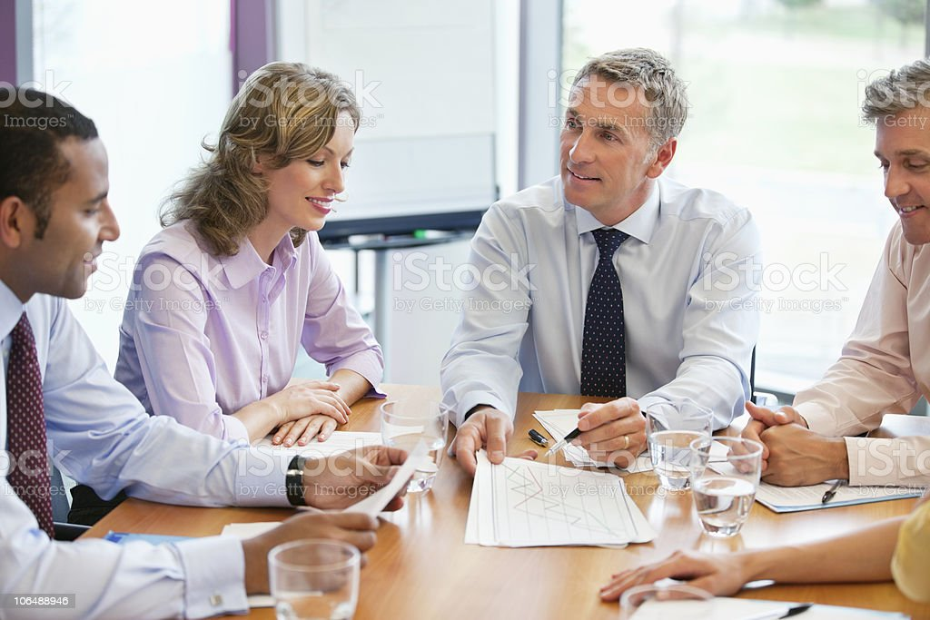 Smiling business people sitting at conference table in a meeting at board room royalty-free stock photo