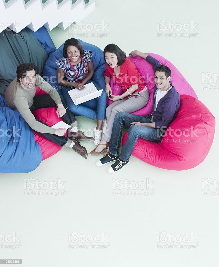 Smiling business people sitting in bean bag chairs royalty-free stock photo