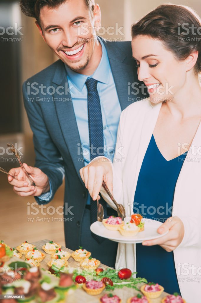 Smiling Business People Taking Snacks from Table stock photo