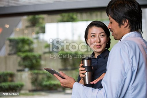 istock Smiling business people using digital tablet 583978648