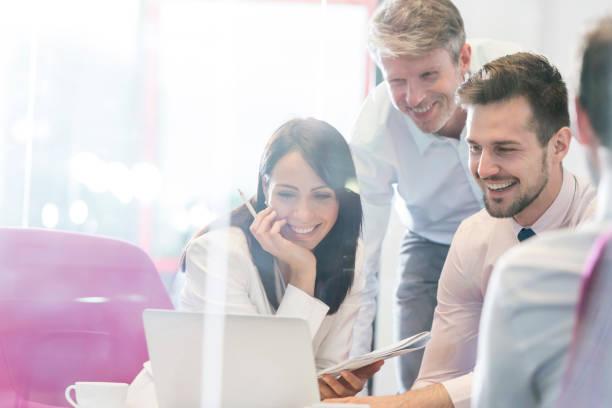 Lächelnde Geschäftsleute, die am Laptop in der Geschäftsstelle im Büro arbeiten – Foto